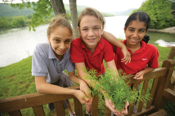 Middle school girl students holding plants