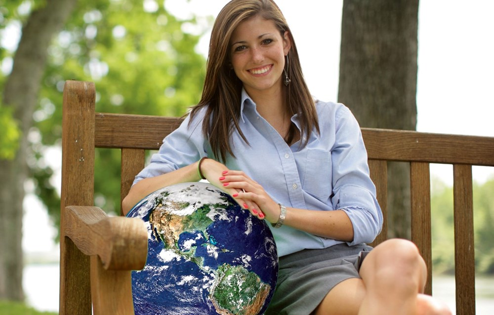 High school student sitting with globe